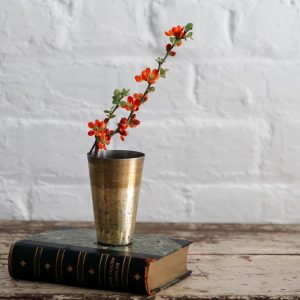 Vintage Lassi glass on a book with spring flowers
