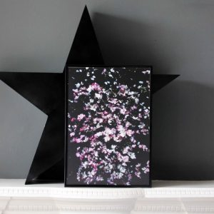 Pink Flowers art print by we are amused in a black frame on a white mantle piece leaning against a black card star cut out and a grey wall 30 x 40