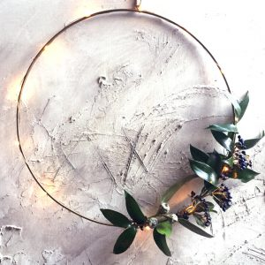 Brass wire ring decorative accessory with foliage and lights wound around it