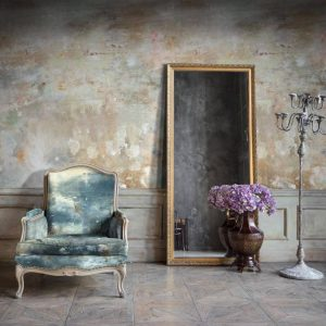 Oh La La Wallpaper in Sand Colour by Feathr at Curious Egg.  Lifestyle image with a regency style armchair in the foreground