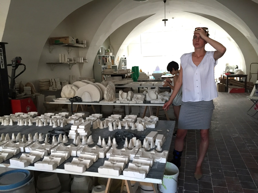 Daniel Pirsc's wife in his porcelain workshop with moulds on table
