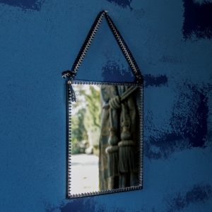 Hanging Mirror with ribbon against blue wall