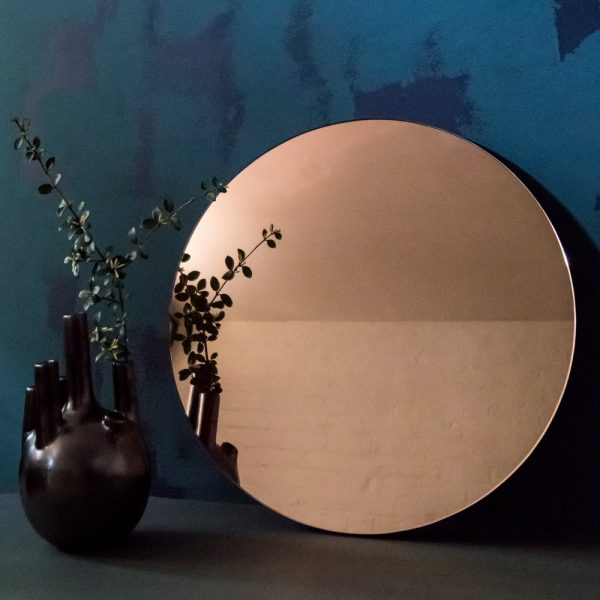 rose gold circular mirror against distressed wall in blue