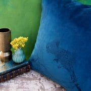 Blue Velvet cushion with bird design against a green background and vase with yellow flowers