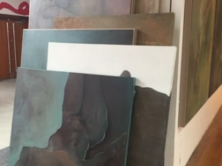 stacked oil paintings leaning against a wall at a degree show