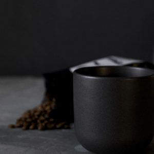 Black ceramic simple mug close up with coffee beans mexican or scandinavian style