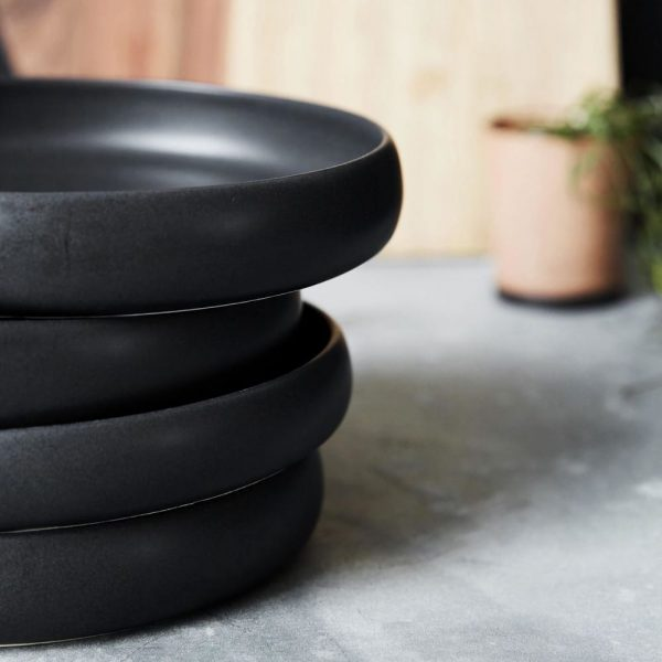Black ceramic stacked plates with raised edge with woodenchopping  boards in the background