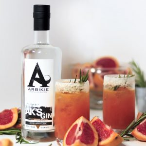 AK's gin bottle with glasses of orange gin cocktail and blood oranges