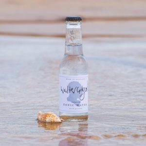 Bottle of Walter Gregor's tonic water on a beach with the tide lapping around it