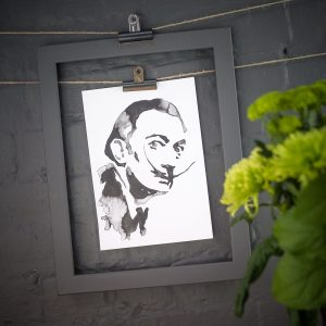 ink blot style image of Salvador Dali art print hanging against a drak grey wall by Jenn Rea