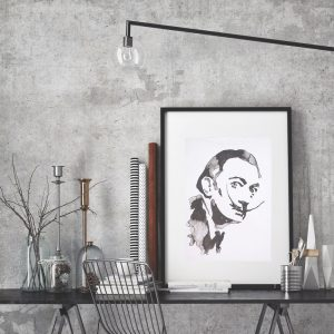Salvador Dali ink blot style print in frame against a grey wall and propped up on a contemporary desk