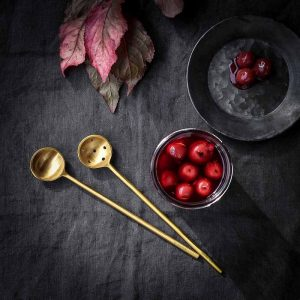 little gold serving utensils with rustic bowls and red sour cherries