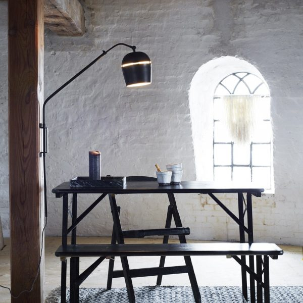 Black metal wall lamp with long metal arm having over a scandinavian table and benches