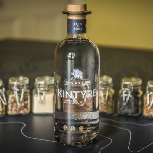 A bottle of Kintyre gin from Beinn an Tuirc distillery with jars of botanicals.  Available from the gin bar at curiousegg.com