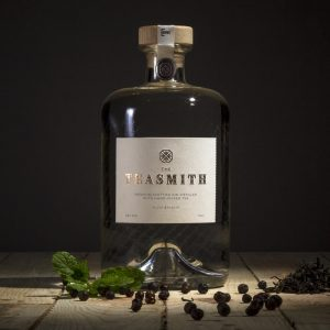 Teasmith gin bottle lifestyle image with dark background and botanicals