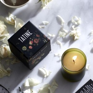 Tatine Peace Rose Candle with flame on marble worktop with Rose petals. Curious Egg.