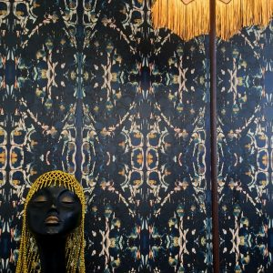 Siouxie Wallpaper by Anna Hayman at Curious Egg. Lifestyle Image with mannequin and lamp in the foreground.