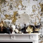 Feathr Safari wallpaper by artist Kiki Slaughter in Gold colourway - lifestyle image with marble fireplace and assorted ornaments.  Curious Egg.