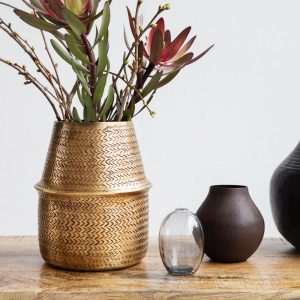 Lifestyle image of woven brass planter
